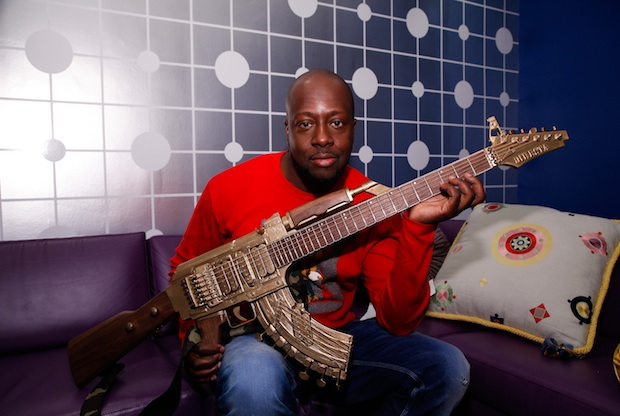 NEW YORK, NY - MAY 01:  Wyclef Jen poses backstage with a guitar shaped like a AK-47 before taping a segment on BET's 106 & Park on May 1, 2013 in New York City.  (Photo by JP Yim/Getty Images for BET)